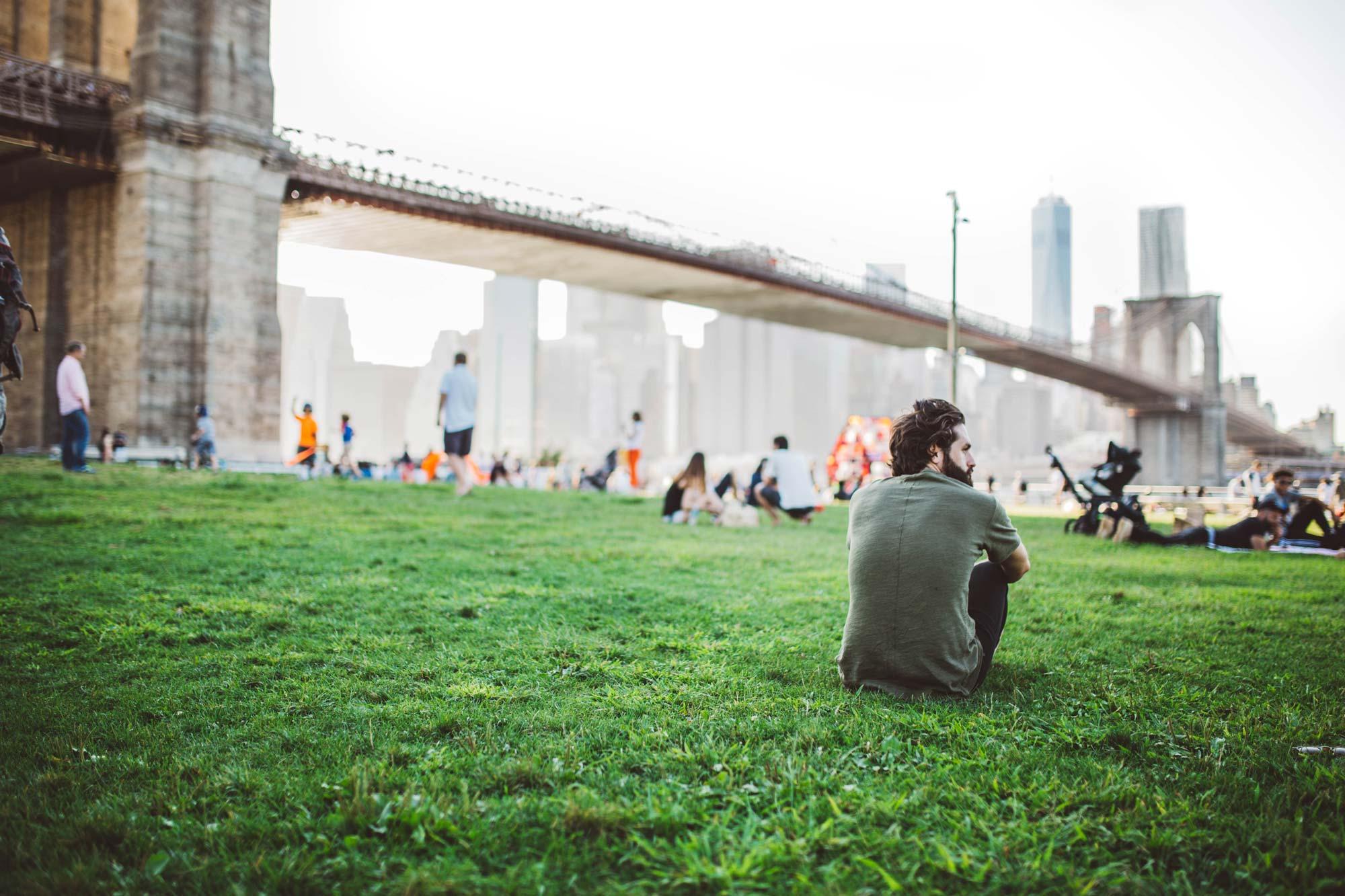 Wertiba Ventures & Liegenschaften: Bild von einem Mann, der nachdenklich am Fuße der Brooklyn Bridge sitzt